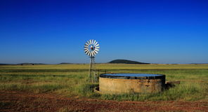 Windmill and dam on farmland, Freestate province, South Africa Stock Image