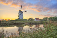 Windmill at sunset. Scenic view of a windmill reflecting on a canal or rover at sunset, Damme, Bruges, Belgium Royalty Free Stock Photography