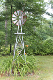 Windmill. Decorative windmill in a lush green garden Royalty Free Stock Photography