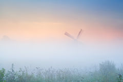 Windmill in dense fog at sunrise Stock Images