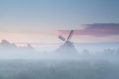 Windmill in dense morning fog Stock Photography