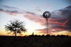 Windmill in desert sunset Royalty Free Stock Image