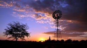Windmill in desert sunset Royalty Free Stock Photo