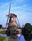 Windmill and dijk, Kinderdijk, Holland. Royalty Free Stock Photo