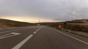 Windmill drive to tunnel. Castilla La Mancha, Spain - 28 August, 2013: Driving in sunset somewhere trough the Spain with farm of wind generators by the side of stock video footage