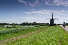 Windmill. Dutch windmill with biker in foreground stock image