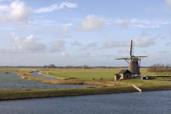 Windmill on Dutch island Texel. Landscape of the Dutch island Texel with a windmill, horses, a blue sky, white clouds, rivers and meadow-land royalty free stock photo