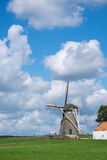 Windmill in dutch landscape. With beautifull white clouds in blue sky Stock Photo