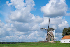 Windmill in dutch landscape. With beautifull white clouds in blue sky Royalty Free Stock Photography