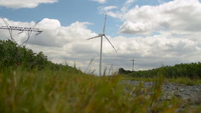 Windmill for electric power production. Windmills Energy. Landscape with Electricity Pylon, Road and Windmills. Wind Turbine Green Energy. Farm with wind power stock video