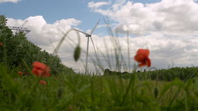 Windmill for electric power production. Windmills Energy. Landscape with Electricity Pylon, Road and Windmills. Wind Turbine Green Energy. Farm with wind power stock video footage