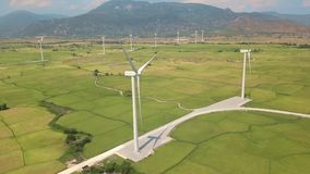 Windmill energy plant power turbine in agricultural field. Aerial view wind power generating farm on green field. And mountain landscape. Generation clean stock footage