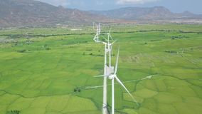 Windmill energy plant power turbine in agricultural field. Aerial view wind power generating farm on green field and. Mountain landscape. Generation clean stock video