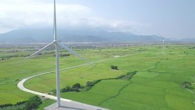 Windmill energy plant power turbine in agricultural field. Aerial view wind power generation on green field and mountain. Landscape. Green clean renewable stock video footage