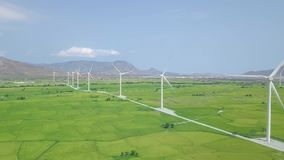 Windmill energy plant power turbine in agricultural field. Aerial view wind power generating farm on green field and. Mountain landscape. Generation clean stock footage