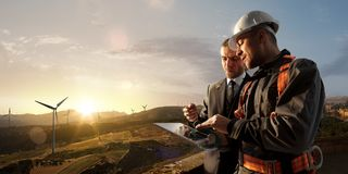 Windmill engineer and businessman planing new ecology project. they standing and looking in tablet. Around wind generators. And beautiful landscape royalty free stock photo