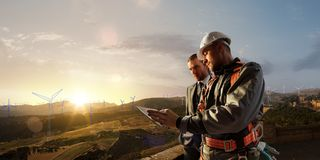 Windmill engineer and businessman planing new ecology project. they standing and looking in tablet. Around wind generators. Blueprint and beautiful landscape stock images