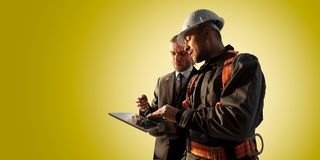 Windmill engineer and businessman planing new ecology project. they standing and looking in tablet. Color studio background. Windmill engineer and businessman stock images