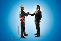 Windmill engineer and businessmans hake hands Color studio background stock photography