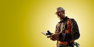 Windmill engineer planing new ecology project. He standing and look in tablet. Color studio background. Windmill engineer planing new ecology project. He royalty free stock image