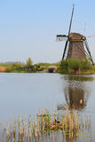 A windmill facing a house with a bird nest on the foreground bottom right corner in vertical view Stock Photography
