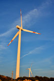 Windmill fan in field. Windmill power generator, under blue sky, shown as energy industry concept Stock Images