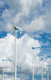 Windmill farm for alternative clean energy with clouds and blue Royalty Free Stock Images