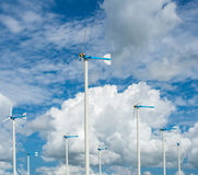 Windmill farm for alternative clean energy with clouds and blue Stock Image