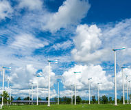 Windmill farm for alternative clean energy with clouds and blue Royalty Free Stock Image