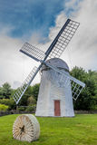 Windmill in a farm field Jamestown Rhode Island. White Windmill with red door next to a stone wheel in Jamestown Rhode Island royalty free stock photo