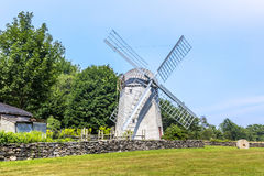 Windmill in a farm by a stone wall in Rhode Island. On the way to Jamestwon this windmill sits in a farm field Royalty Free Stock Photos
