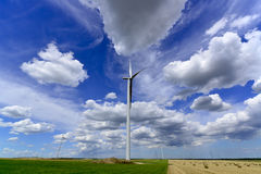 Windmill farm turbines with beautiful grey white. Clouds on green and haystack fields Stock Photography