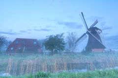 Windmill and farmhouse in fog Royalty Free Stock Images
