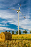 Windmill on the field as a symbol of green energy Stock Photo