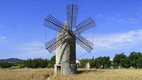 Windmill on field on Mallorca. Typical mallorquin windmill on a wheat on the Spanish island in the Mediterranean island of Majorca and green trees against a blue Royalty Free Stock Images