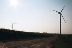 Windmill on field. White windmills on a green field of corn in late summer. / Windmill on field. / Belarus Royalty Free Stock Photos