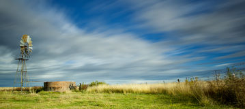 Windmill and fields. A windmill and fields of grass under cloudy skies Royalty Free Stock Image
