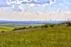 Windmill fields land. Yellow windmill arable blue clouds cultivation fields green land plowing rays soil trees agriculture stock photography