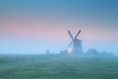 Windmill in fog at sunrise Stock Image