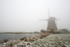 Windmill on a foggy winter morning Stock Photos
