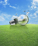 Windmill and forest inside light bulb with birds over green gras Stock Photography