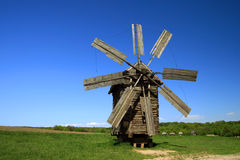 Windmill with fresh green grass and clear blue sky Stock Photos