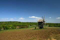 Windmill with fresh green grass and clear blue sky Royalty Free Stock Photo