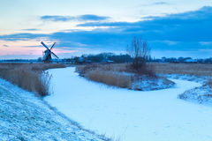 Windmill and frozen river in snow Royalty Free Stock Image