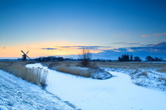 Windmill by frozen river at sunrise, Groningen Royalty Free Stock Photography