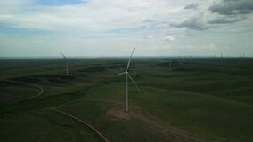 A windmill for generating electricity, standing on a green field.