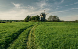 Windmill in green field on blue sky background with white clouds Royalty Free Stock Photography