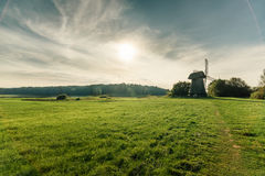 Windmill in green field on blue sky background with white clouds Royalty Free Stock Photos