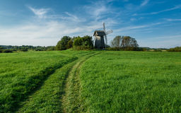 Windmill in green field on blue sky background with white clouds Stock Images