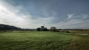windmill in green field on blue sky background with white clouds Stock Photos